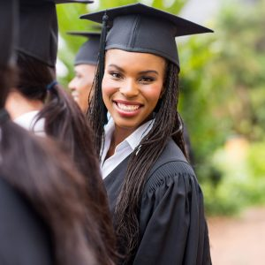 Pretty university graduate looking back at graduation ceremony